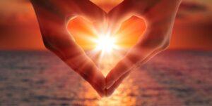 visualizes bliss, photo of hands in heart shape framing ocean sunset
